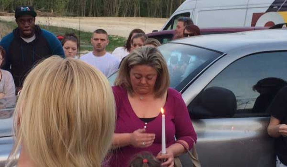 Brandi Stewart holds a candle at the vigil for her daughter.