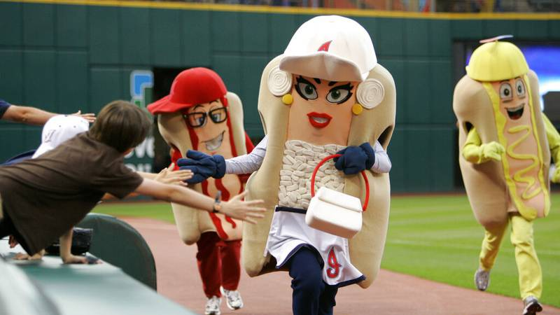 Fans reach out to the performers in the hot dog race during a baseball game Monday, June 29,...
