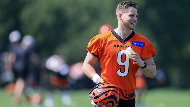 Cincinnati Bengals Joe Burrow smiles as he takes the field during an NFL football camp practice...