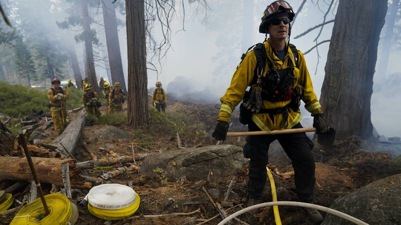 Will Fitch, fire captain from Cosumnes Fire Department, and his crew hold a fire line to keep...