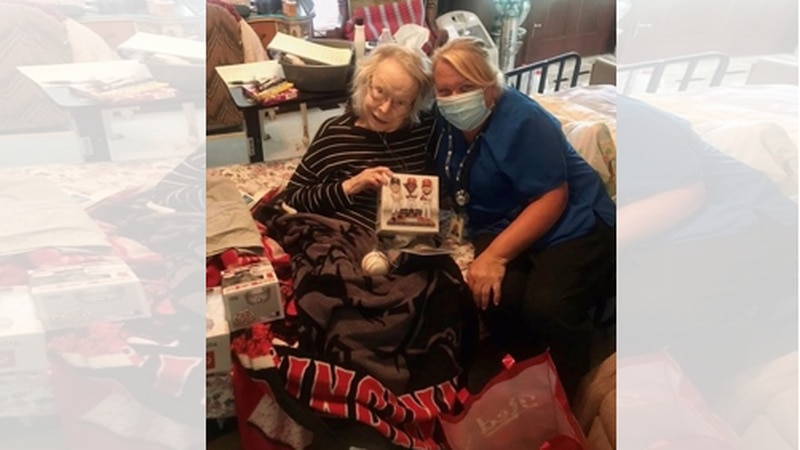 Reds fan Eva Newman shows off her gifts from the team along with RN Case Manager Rhonda...
