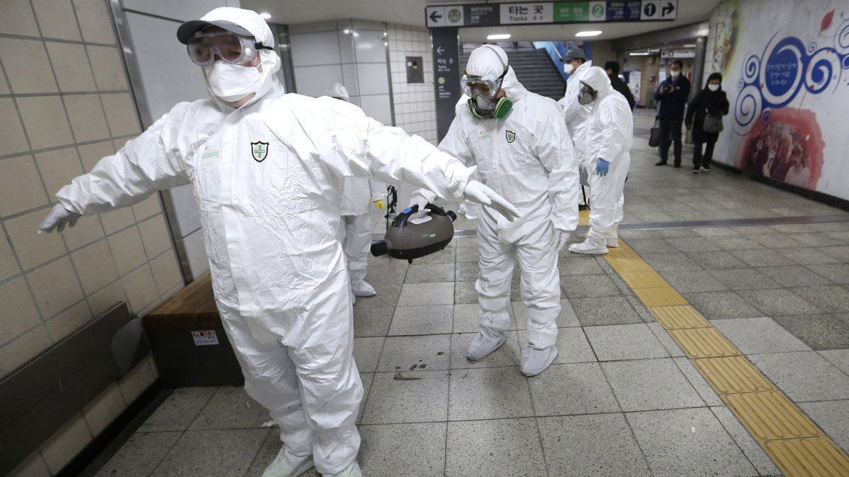 Workers wearing protective gears help clean each other's suits after disinfecting as a...