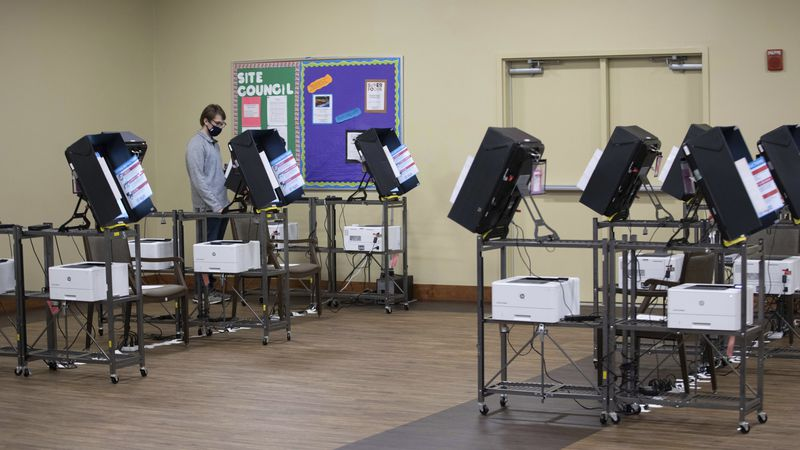 A man votes on the only machine working shortly after polls opened in Georgia's Senate runoff...