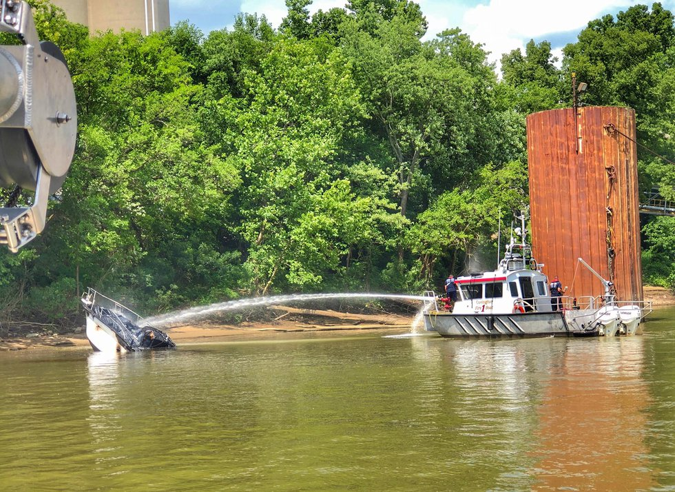 Officials fight a fully engulfed boat fire near Villa Hills Marina on Sunday afternoon....