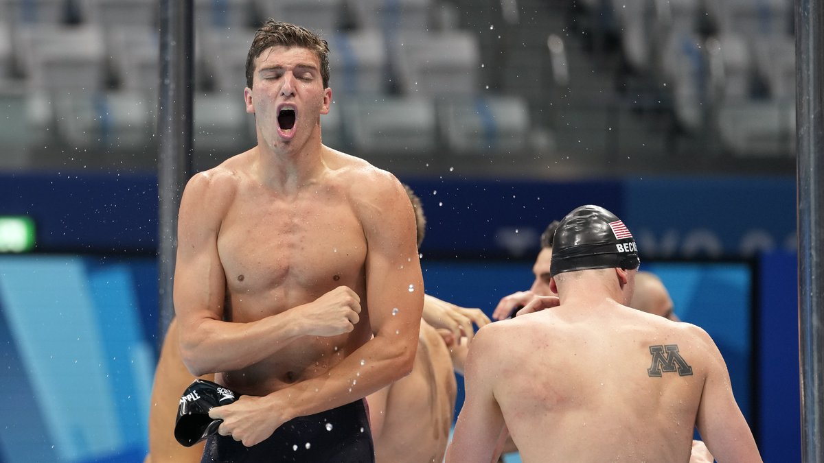 Zach Apple of the United States men's 4x100m freestyle relay team celebrates after winning the...