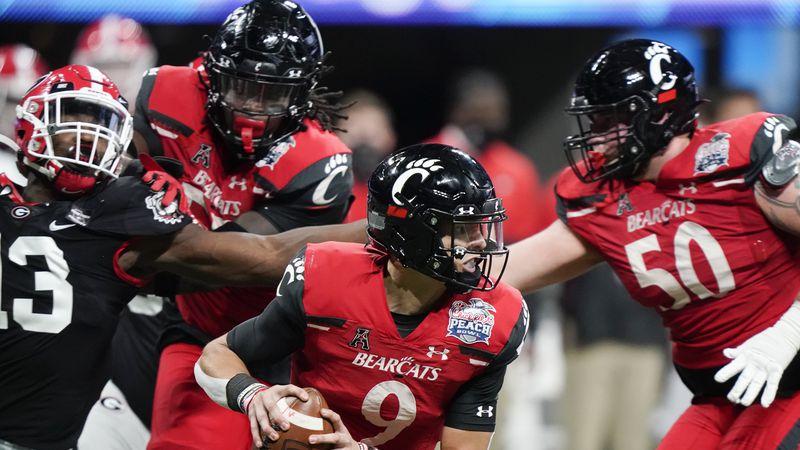 Cincinnati quarterback Desmond Ridder (9) runs out of the pocket against Georgia during the...