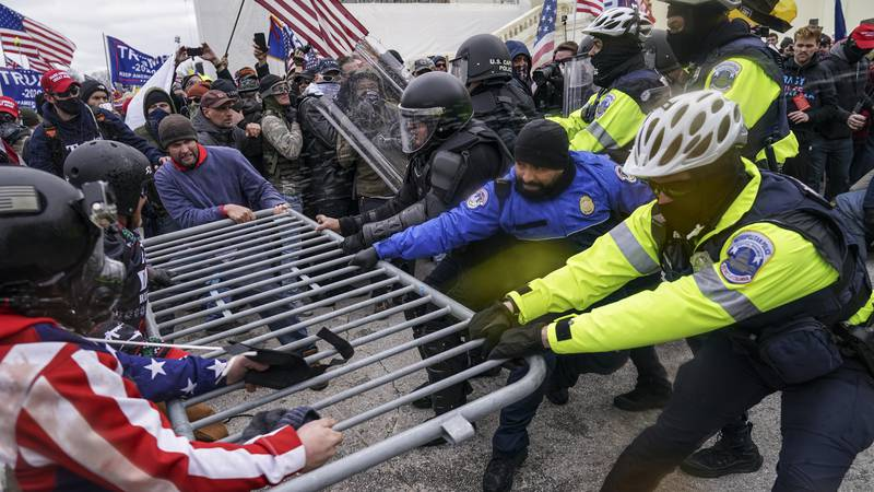 FILE - In this file photo from Wednesday, Jan. 6, 2021, Trump supporters beset a police barrier...
