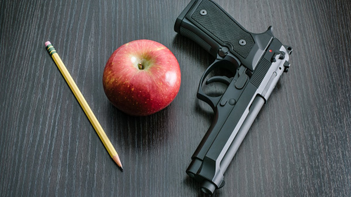 9mm Beretta 92FS type handgun with apple and pencil depicting the question whether to arm...