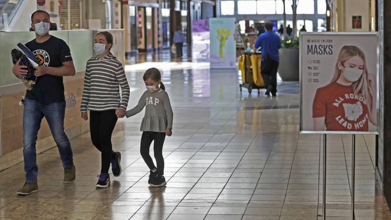 Shoppers walks past a sign encouraging masks at SouthPark Mall in Strongsville, Ohio.