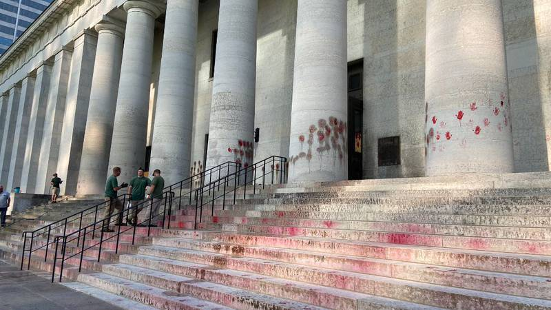 On Thursday vandals used red paint to put hand prints all over the front of the Statehouse in...