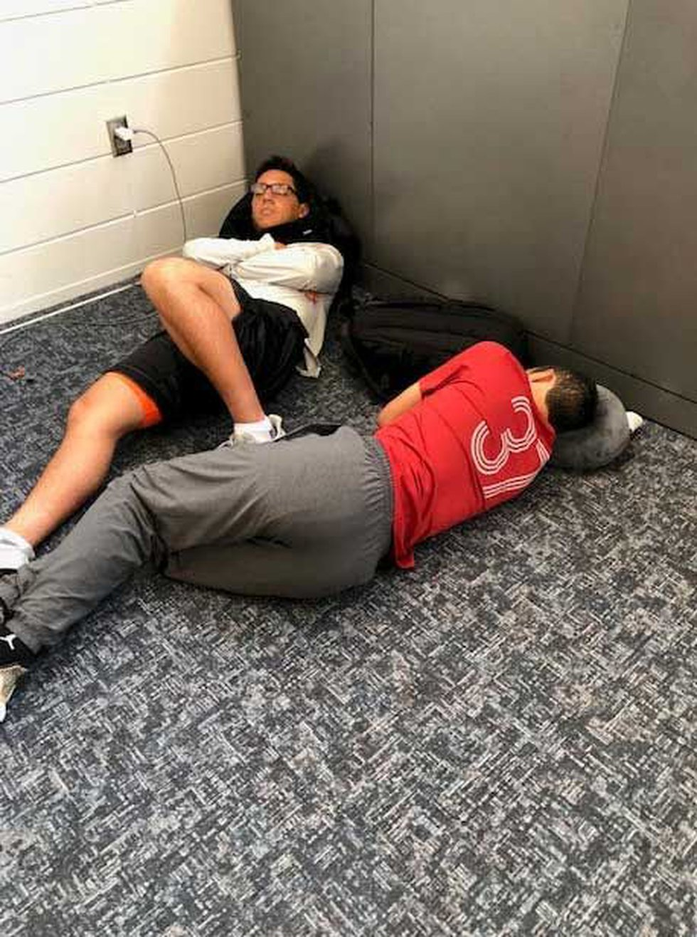 WOW air passengers crash on the floor as they wait for their flight Tuesday. (Photo: Provided...