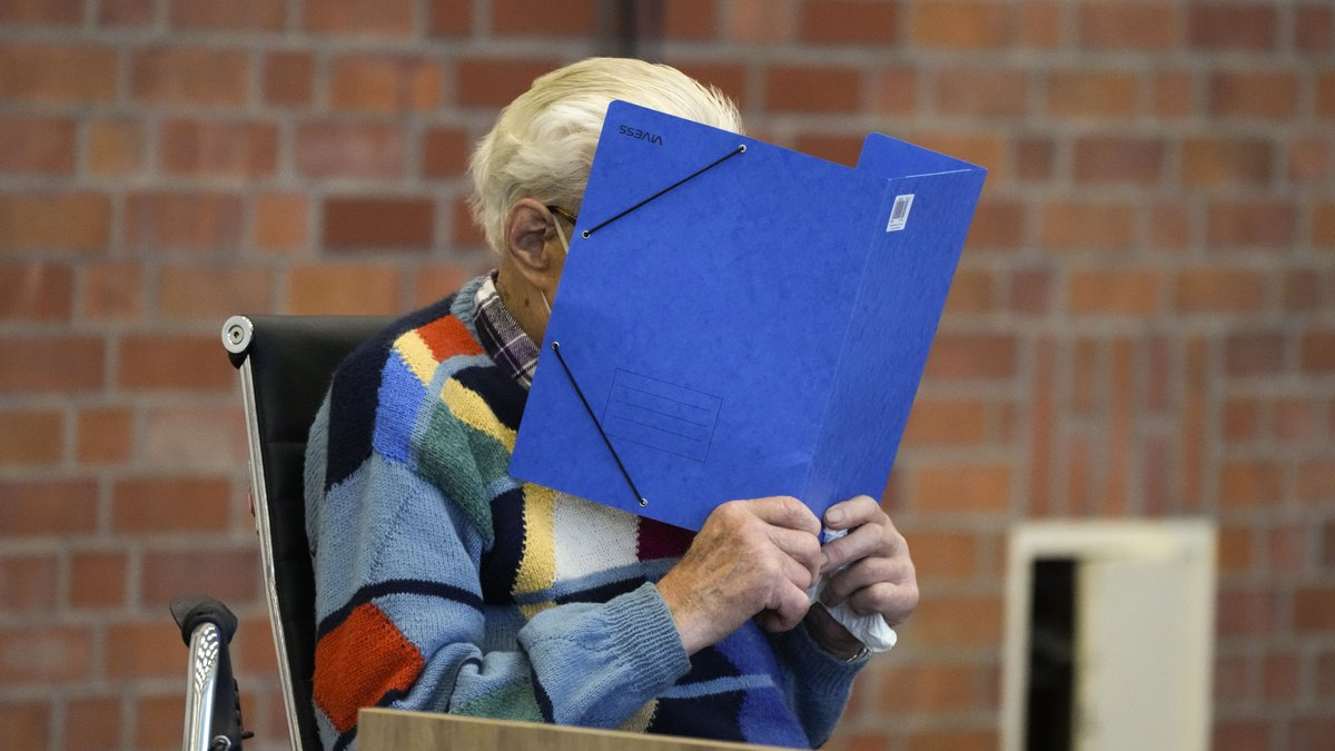 The accused Josef S. covers his face as he sits in the courtroom in Brandenburg, Germany,...