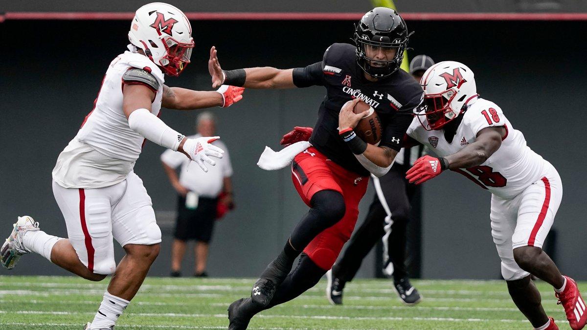 Cincinnati quarterback Desmond Ridder, center, runs the football during the first half an NCAA...
