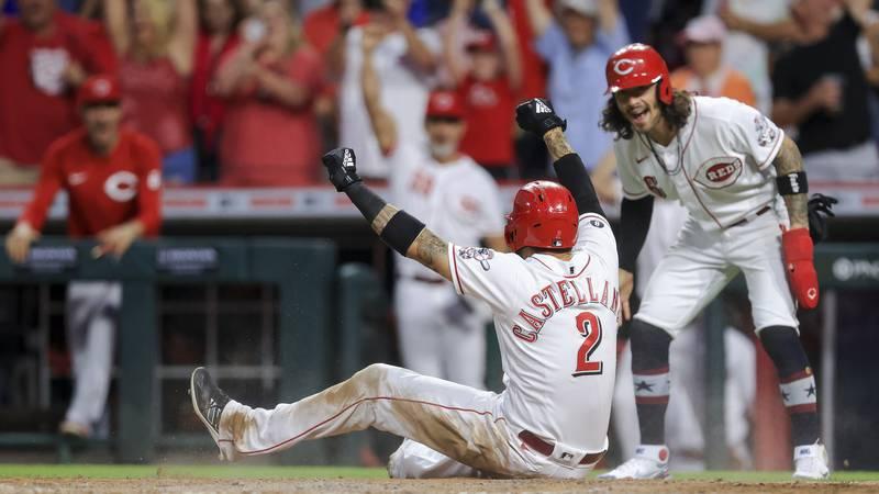 Cincinnati Reds' Nick Castellanos (2) celebrates after scoring a run on a two-run RBI-double by...